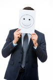 Businessman holding white card with face on it Royalty Free Stock Photography