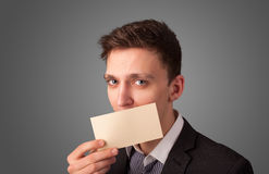 Businessman holding white card at front of her lips with copy sp Royalty Free Stock Photos
