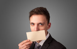 Businessman holding white card at front of her lips with copy sp Stock Images