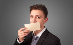 Businessman holding white card at front of her lips with copy sp Royalty Free Stock Photography
