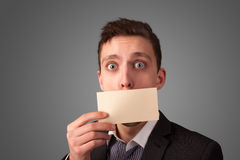 Businessman holding white card at front of her lips with copy sp Royalty Free Stock Images