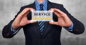 Businessman holding white card with Service Five Stars sign, Gre Stock Images