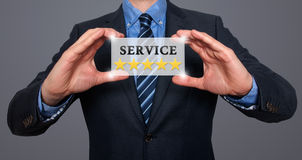 Businessman holding white card with Service Five Stars sign, Gre Royalty Free Stock Image