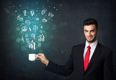 Businessman holding a white cup with business icons. Businessman standing and holding a white cup with business icons coming out of the cup Royalty Free Stock Photography