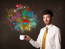 Businessman holding a white cup with diagrams and graphs Stock Images