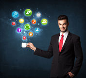 Businessman holding a white cup with setting icons Royalty Free Stock Photography