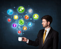 Businessman holding a white cup with setting icons Stock Images