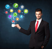 Businessman holding a white cup with setting icons Stock Photo