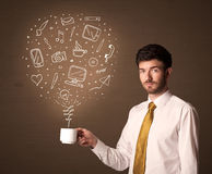 Businessman holding a white cup with social media icons Stock Photo