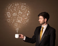 Businessman holding a white cup with social media icons Royalty Free Stock Image