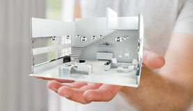 Businessman holding white 3D rendering apartment in his hand. Businessman on blurred background holding white 3D rendering apartment in his hand Royalty Free Stock Image