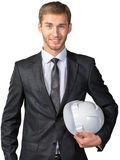 Businessman holding white hardhat. Young businessman holding white hardhat Royalty Free Stock Photo