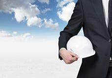 Businessman holding white helmet. Businessman holding helmet on blue sky background Stock Images