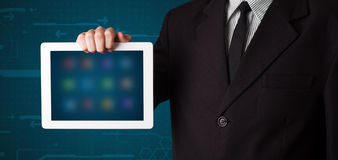 Businessman holding a white modern tablet with blurry apps Royalty Free Stock Images