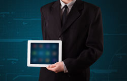 Businessman holding a white modern tablet with blurry apps Stock Photos