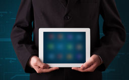 Businessman holding a white modern tablet with blurry apps Royalty Free Stock Photos