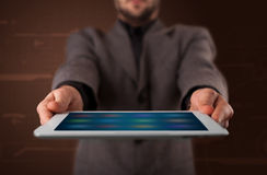 Businessman holding a white modern tablet with blurry apps Royalty Free Stock Image