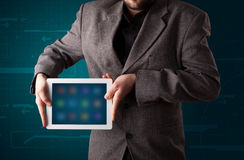 Businessman holding a white modern tablet with blurry apps Stock Photography
