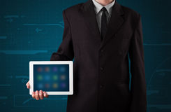 Businessman holding a white modern tablet with blurry apps Stock Images