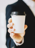 Businessman holding white paper coffee cup to take away.Mock up of carton coffee cup for go outside.Vertical mockup Stock Photo