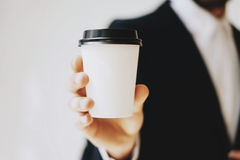 Businessman holding white paper coffee cup to take away.Mock up of clean carton coffee cup.Horizontal mockup, blurred Stock Images