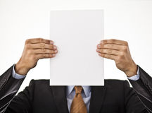 Businessman holding white paper in front of his fa Royalty Free Stock Image
