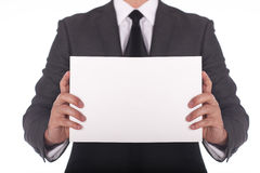 Businessman holding a white piece of paper. Royalty Free Stock Photography