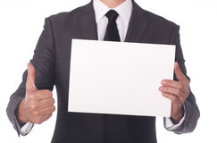 Businessman holding a white piece of paper. Stock Photo