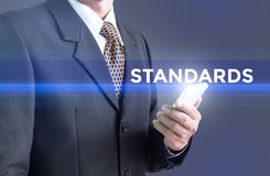A Businessman holding a white sign with the message standards. Stock Photo