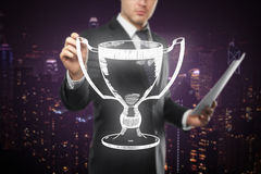 Businessman holding winner's cup. Businessman with paperwork holding abstract winner's cup sketch on city background stock photos