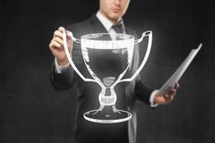 Businessman holding winner's cup sketch. Businessman with paperwork holding abstract winner's cup sketch on concrete background stock image