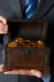 Businessman Holding Wooden Chest With Gold Coins Inside. Businessman Holds Wooden Chest With Gold Coins Inside stock photo