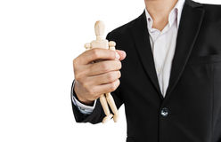 Businessman holding wooden figure, concept of take control, oppress, and etc., isolated on white background Royalty Free Stock Images