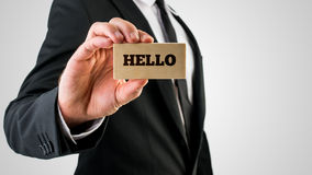 Businessman holding a wooden sign saying Hello Royalty Free Stock Images