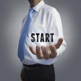 Businessman holding the word start Stock Photo