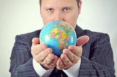 Businessman is holding the world stock photos