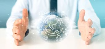 Businessman holding a World globe surronding by ecology icons and connection 3d rendering. View of a Businessman holding a World globe surronding by ecology stock photography