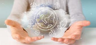 Businessman holding a World globe surronding by ecology icons and connection 3d rendering. View of a Businessman holding a World globe surronding by ecology stock photos