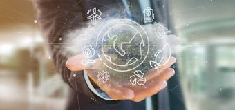 Businessman holding a World globe surronding by ecology icons an. View of a Businessman holding a World globe surronding by ecology icons and connection 3d royalty free stock photo