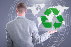 Businessman holding world Recycle. Businessman holding a virtual green recycle sign in hand royalty free stock photos