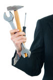 Businessman holding wrench, hammer and screwdriver. Isolated on white Royalty Free Stock Image