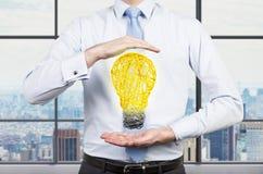 Businessman holding yellow bulb Royalty Free Stock Image
