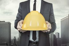 Businessman holding yellow helmet in hands on. Businessman holding yellow helmet in hands with tie and shirt on cityscape background royalty free stock photography