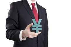 Businessman holding yen sign Stock Photo