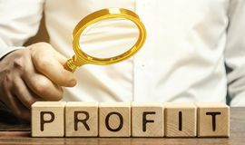 Free Businessman Holds A Magnifying Glass Over The Word Profit. The Concept Of Profitability And Performance Of Business. Analysis Of Stock Photos - 160534313