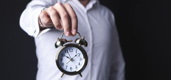 Businessman holds an alarm clock stock images