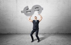 Businessman holds a big heavy concrete dollar object with sleeves rolled up. Stock Photography