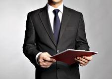 Businessman holds a  booklet Royalty Free Stock Image