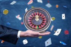 A businessman holds a casino roulette on his palm on a background of chips and cards. Business and chance. Playing your cards right. High stakes royalty free stock photo