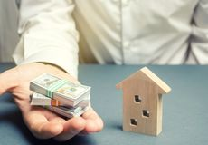Businessman holds dollars in hands near wooden house. Real estate investment concept. Mortgage. Loan for housing. Credit. Rent. Rental. Buying a property. The stock photography